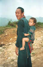 to Jpeg 30K Black Hmong man carrying his granddaughter on his back in a baby carrier in the hills around Sa pa, Northern Vietnam 9510I28