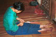 to Jpeg 44K 9511A02 Weaving a braid with the warp tension achieved between toes and a tie around the waist. Although the braid is narrow quite a complicated shed is set up. Luong village on the road from Sa Pa to Lao Cai town, Lao Cai province.