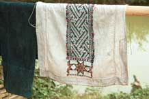 to Jpeg 37K 9511A10 Dao Quan Trang woman's bodice hanging out to dry and showing the reverse side of the embroidery with the characteristic stars at the base. The background fabric is probably cottton. Luong village on the road from Sa Pa to Lao Cai town, Lao Cai province.