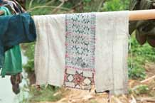 to Jpeg 39K 9511A11 Dao Quan Trang woman's bodice hanging out to dry and showing the reverse side of the embroidery with the characteristic stars at the base. The background fabric appears to be hand spun and woven and is probably cottton. Luong village on the road from Sa Pa to Lao Cai town, Lao Cai province.