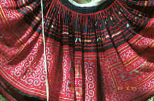 to Jpeg 54K Detail of Red Hmong (Lai Chau province, northern Vietnam) woman's skirt showing the waist gathering, applied strips of red fabric and small triangles to the top border and cross-stitch with applied floral rectangles in the bottom border 9510f27.jpg